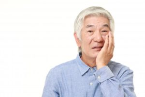 older man with loose dental implant
