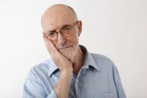 man experiencing pain from dentures